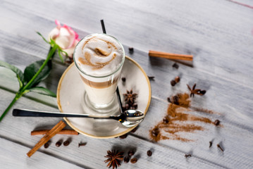 A glass of latte on the white wooden background