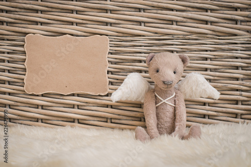 A teddy bear with angel wings sits on the background of a wicker basket. Blank form Kindness, hope, keeper,