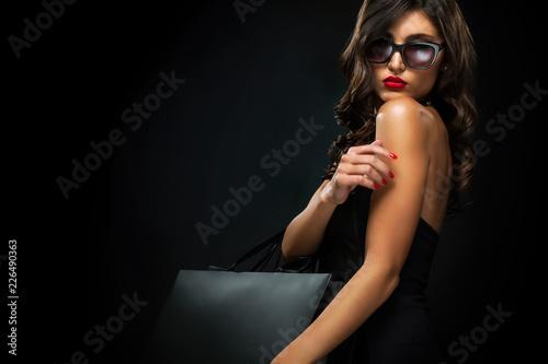 Czarny piątek koncepcji sprzedaży. Zakupy kobieta trzyma popielatą torbę odizolowywającą na ciemnym tle w wakacje