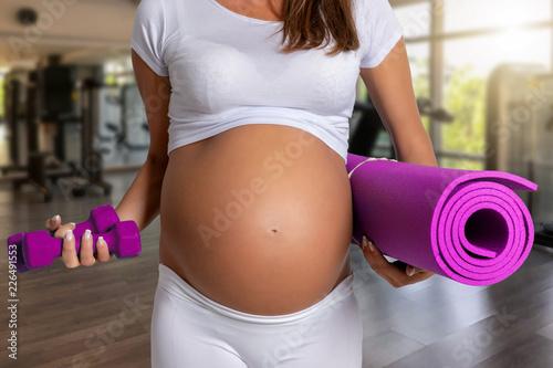 Leinwanddruck Bild Schwangerschaft und Fitness Konzept: schwangere Frau mit Yoga Matte im Fitnessstudio