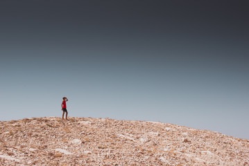 exploring - lonely human walking in a rocky desert - freedom and adventure lifestyle and sport concepts