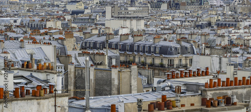 The roofs of Paris and its chimneys under a clouds sky - 226500312