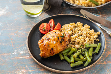 Grilled chicken thighs with bulgur, asparagus beans and tomatoes. Delicious lunch. Copy space.