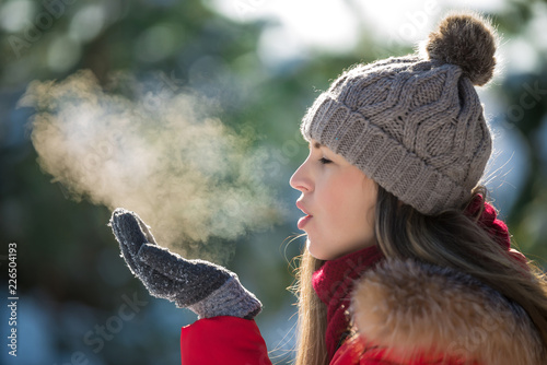 Leinwanddruck Bild Attractive young woman breathe out steam outdoor in winter