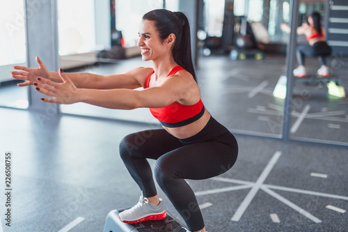 Poster Cheerful female squatting on step