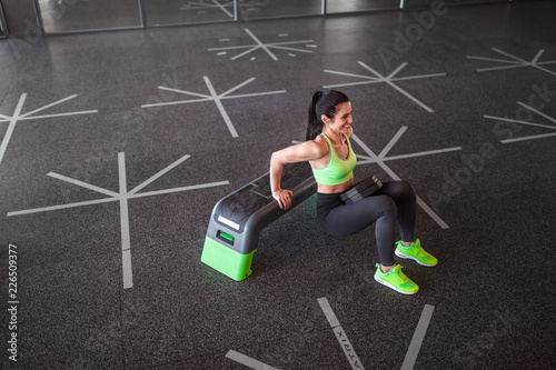 Leinwanddruck Bild Cheerful woman performing dips near step