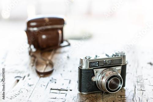 Schöne vintage Kamera im Vordergrund steht auf Holztisch mit eingeschnitzen Initialen und Namen der Hintergrund verläuft ins helle nach draußen © Petra