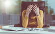 Leinwanddruck Bild - Desperate businesswoman with head in hands, light effect