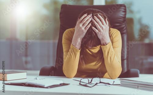 Leinwanddruck Bild Desperate businesswoman with head in hands, light effect
