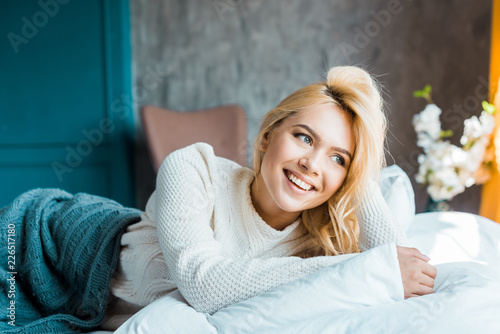Leinwandbild Motiv happy attractive woman in sweater lying under blanket on bed in bedroom and looking away