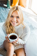 Leinwandbild Motiv smiling attractive woman in sweater holding cup of coffee and looking at camera in bedroom in morning