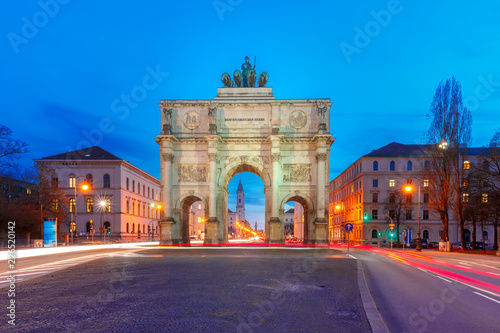 The Siegestor or Victory Gate, triumphal arch crowned with a statue of Bavaria with a lion-quadriga, at night in Munich, Germany