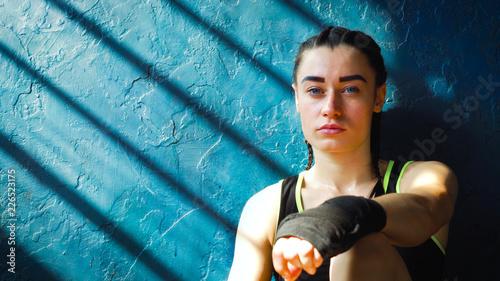 Zbliżenie portret mieści białego żeńskiego boksera obsiadanie na podłogowy pobliski ścienny odpoczywać po trenować przy gym bezpłatną przestrzenią, copyspace. Młoda brunetka dziewczyna bierze breake. Wellness, koncepcja motywacji
