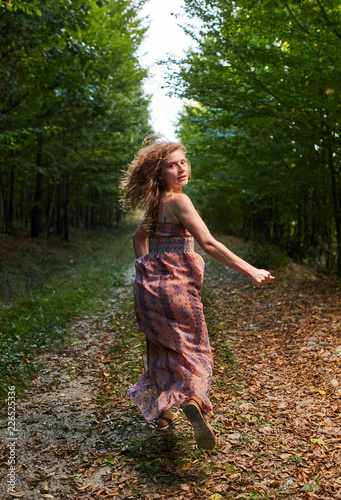 Foto Murales Scared girl running through forest