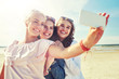 Leinwandbild Motiv summer vacation, holidays, travel, technology and people concept- group of smiling young women taking sulfide with smartphone on beach