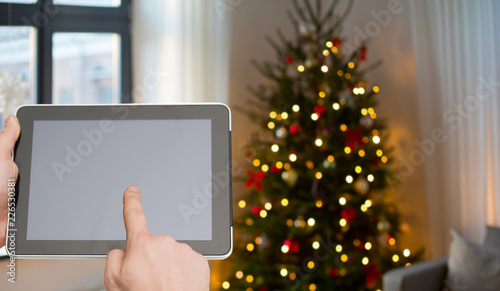 holidays and technology concept - close up of male hands with tablet pc over christmas tree lights background