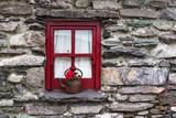 Vintage flower pot rusty kettle on window of old style Irish cottage
