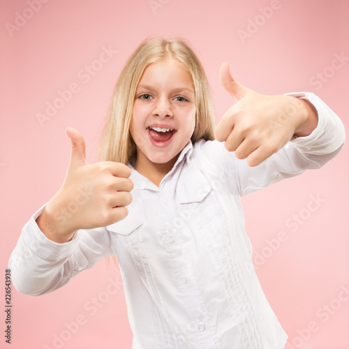 Leinwandbild Motiv Happy teen girl standing, smiling isolated on trendy pink studio background. Beautiful female portrait. Young satisfy girl with sign ok. Human emotions, facial expression concept. Front view.