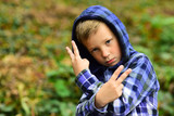 Casually cool. Cool boy. Small boy in casual hoodie. Small child show insulting gesture. Im a bit of a bad boy. My image is cool - 226544763