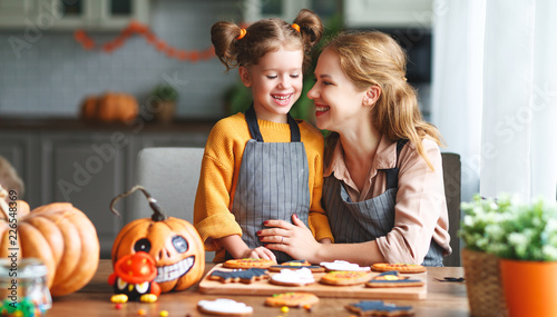 Leinwandbild Motiv happy Halloween! family mother and daughter getting ready for   holiday and baking cookies