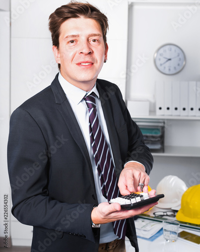Young man worker calculating in the office on the computer - 226554302
