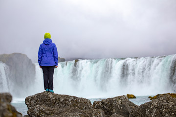 A beautiful young woman is standing against the backdrop of a beautiful waterfall. Iceland © sergeimalkov13