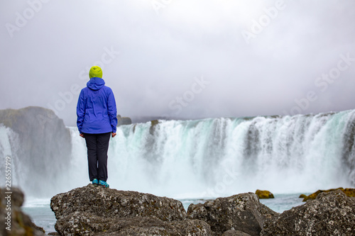 A beautiful young woman is standing against the backdrop of a beautiful waterfall. Iceland - 226557919