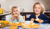 Two little girls enjoying pastry with cream - 226559525