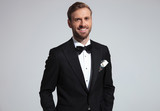 portrait of a relaxed laughing young elegant man in tuxedo