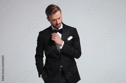 Leinwandbild Motiv sexy elegant man in tuxedo looks down and poses