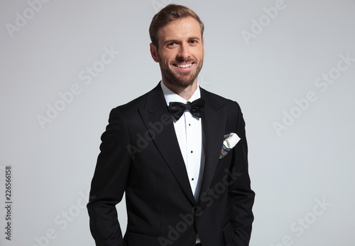 Leinwandbild Motiv portrait of a relaxed laughing young elegant man in tuxedo