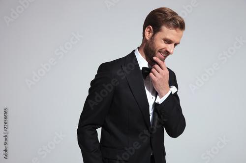 Leinwandbild Motiv side view of an elegant man laughing and thinking