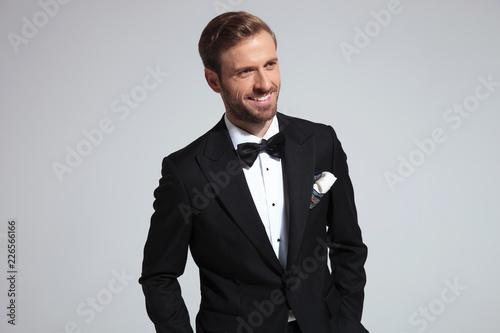 Leinwandbild Motiv cool elegant man in tuxedo is laughing while looking away
