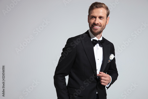 Leinwanddruck Bild happy young elegant man smiles and looks to side