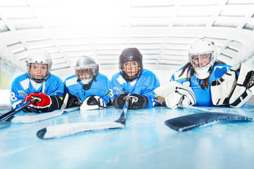 Young hockey players laying on ice rink in line