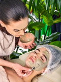Mud facial mask of woman in spa salon. Cleansing purifying and massage with clay full face. Beautician wearing medical hat and brushon in therapy room.
