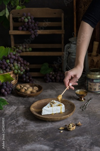Poster Brie cheese on a wooden plate. With grapes, nuts and honey