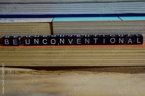 Be unconventional on wooden blocks. Motivation and inspiration concept. Cross processed image