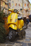 tabby cat sits near a bright yellow scooter on the street in the evening