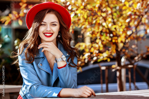 Leinwanddruck Bild Outdoor portrait of young beautiful happy smiling girl with long hair, red lips, wearing stylish hat, blue jacket posing in autumn street. Lifestyle, autumn fashion concept. Copy, empty space for text