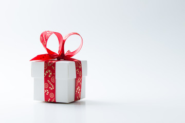 One white gift box tied with a red Christmas theme ribbon isolated on white background