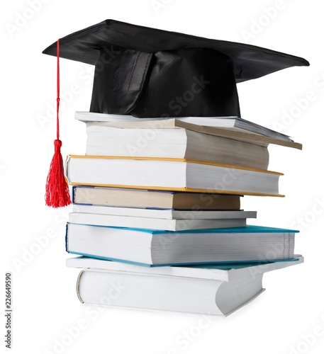 Obraz na płótnie stack of different colored books with a graduation cap