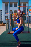 Girl on street workout listens to music on headphones and drinks water from a bottle. She is wearing blue sports clothes. Healthy lifestyle.