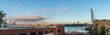 A panoramic of New Jersey across the Hudson River from Manhattan early in the morning. A building is on the left and a crane and building are on the right. The sky is blue with white clouds