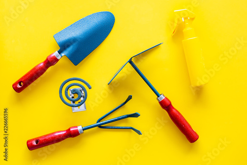 Foto Murales Mosquito protection for garden. Mosquito coil and spray near garden tools on yellow background top view