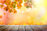 Multi colored autumn leaves bokeh background over wooden deck