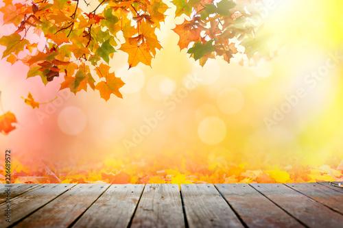 Leinwandbild Motiv Multi colored autumn leaves bokeh background over wooden deck