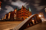 Old Speicherstadt in Hamburg illuminated at night. Arch bridge and historical buildings. Warehouse District -Speicherstadt Landmark of HafenCity quarter