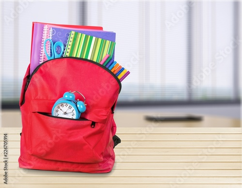 Blue school backpack on wooden table