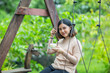 Asian girl on wooden swing and enjoy with her green tea
